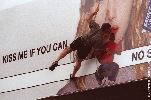 Royce Lemberg takes up the Smint challenge, kissing a billboard
