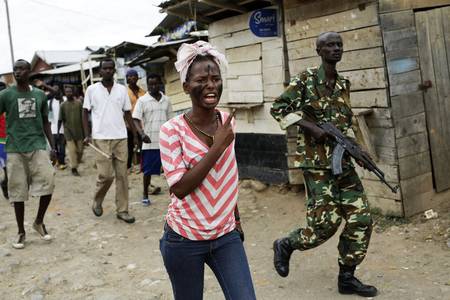 A soldier walks along with demonstrators shouting at police dismantling a barricade in the Kanyosha  district of  Bujumbura, Burundi, Wednesday May 6, 2015. (Photo by Jerome Delay/AP Photo)