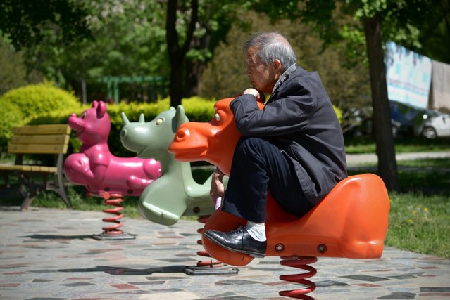 An elderly man sits on a hobby horse at a residential area in Beijing on May 4, 2015. (Photo by Wang Zhao/AFP Photo)