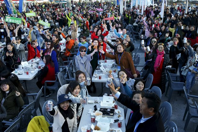 Chinese tourists make a toast with canned drinks and fried chicken pieces during an event organized by a Chinese company at a park in Incheon, South Korea, March 28, 2016. (Photo by Kim Hong-Ji/Reuters)