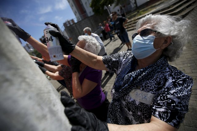 Women spray their designs on a wall during a graffiti class offered by the LATA 65 organization in Lisbon, Portugal May 14, 2015. The LATA 65 organization is an initiative for the elderly in the area of urban art. Since it began in 2012, they have introduced the world of graffiti to over 100 senior citizens, giving workshops in different neighborhoods of Lisbon. (Photo by Rafael Marchante/Reuters)