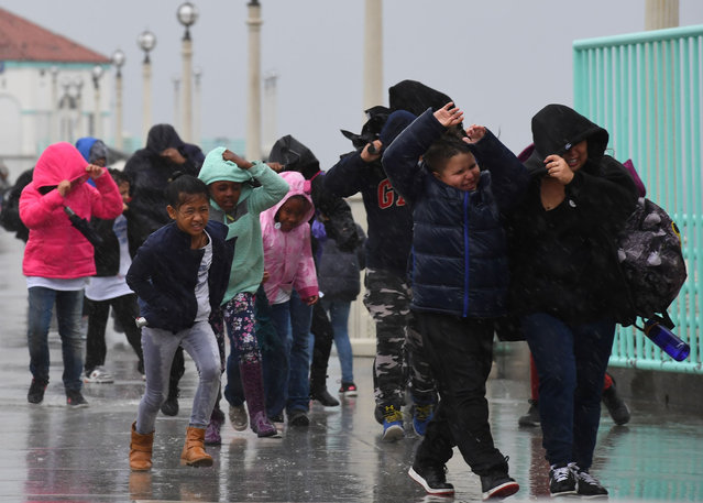 Schoolchildren race back to their bus after getting caught in heavy rain during a school excursion, as the strongest storm in six years slams Los Angeles, California, on February 17, 2017. (Photo by Mark Ralston/AFP Photo)