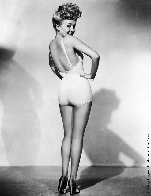 Portrait of American model and actress Betty Grable, as she stands in high heels and a one-piece bathing suit and looks  over her shoulder, one hand on her waist, 1943