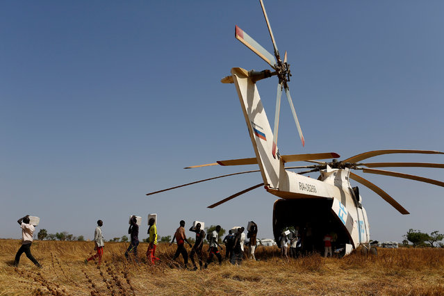 Men unload boxes of nutritional supplements from an helicopter prior to a humanitarian food distribution carried out by the United Nations World Food Programme (WFP) in Thonyor, Leer county, South Sudan, February 25, 2017. (Photo by Siegfried Modola/Reuters)