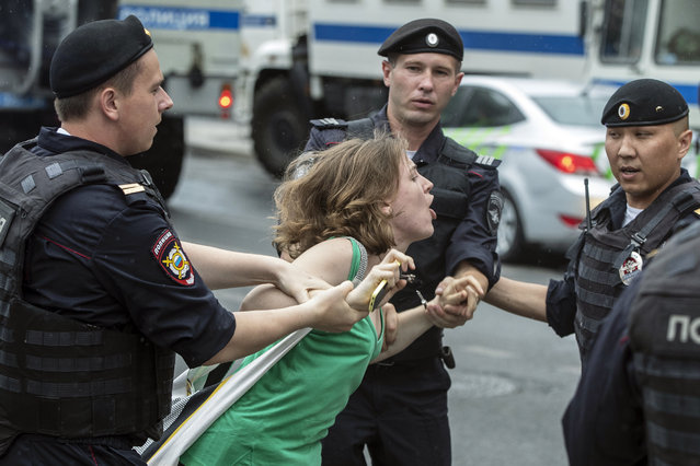 Police officers detain a woman during a march in Moscow, Russia, Wednesday, June 12, 2019. Police and hundreds of demonstrators are facing off in central Moscow at an unauthorized march against police abuse in the wake of the high-profile detention of a Russian journalist. More than 20 demonstrators have been detained, according to monitoring group. (Photo by Pavel Golovkin/AP Photo)