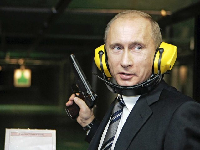 Russian President Vladimir Putin holds a pistol during his visit to a newly-built headquarters of the Russian General Staff's Main Intelligence Department (GRU) in Moscow, 08 November 2006. (Photo by AFP Photo/ITAR-TASS)