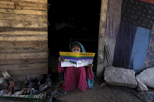 A girl looks at a book while sitting at the entrance of her school in Lahore, Pakistan, May 15, 2015. (Photo by Mohsin Raza/Reuters)