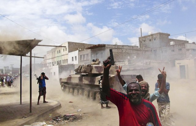 Southern Popular Resistance fighters react as one of their tanks fire at a Houthi position during fighting in Yemen's southern city of Aden May 7, 2015. (Photo by Reuters/Stringer)