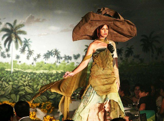 A Cuban model displays a hat shows off a creation with a tobacco leaf motif, 28 February 2003, during a fashion show at Havana's 5th Cigar festival in Cuba. (Photo by Adalberto Roque/AFP Photo)