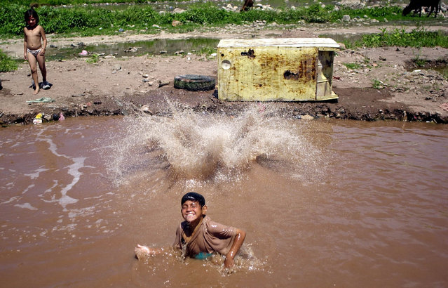 Children play in water near the Choluteca River to cool off from the high temperatures in Tegucigalpa, Honduras Tuesday, March 4, 2003. The Choluteca is the most polluted river in the country. (Photo by Ginnette Riquelme/AP Photo)