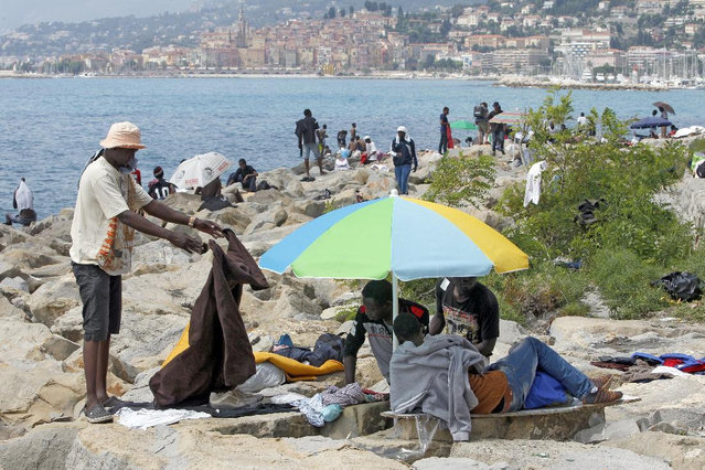 Migrants crowd on the rocky beach at the Franco-Italian border near Menton, southeastern France, Tuesday, June 16, 2015. Some 100 migrants, principally from Eritrea and Sudan, attempted since last Friday, to cross the border from Italy and have been blocked by French and Italian gendarmes. (AP Photo/Lionel Cironneau)