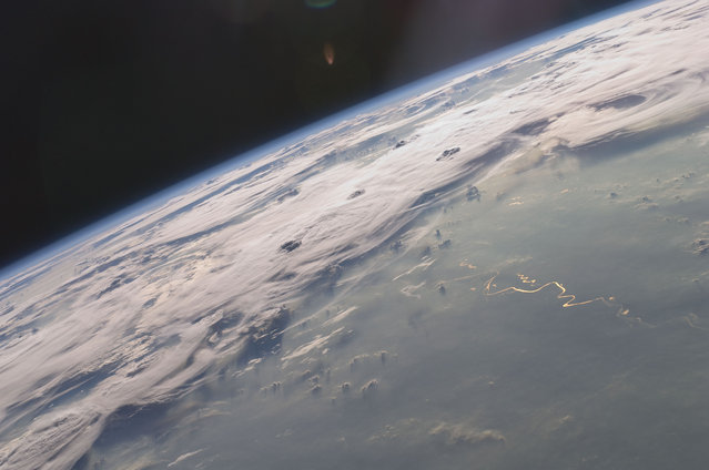 A picturesque line of thunderstorms and numerous circular cloud patterns filled the view as the International Space Station (ISS) Expedition 20 crew members looked out at the limb (blue line on the horizon) of the Earth. (Photo by NASA)