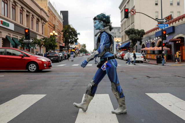 A women in costume walks across the downtown intersection during the spring night of the pop culture festival Comic Con International in San Diego, California,U.S., July 17, 2019. (Photo by Mike Blake/Reuters)