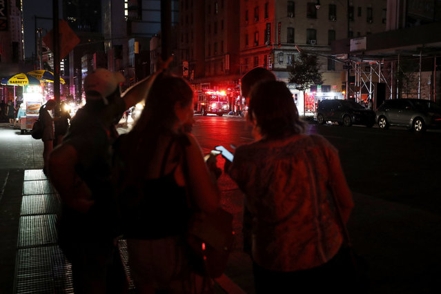 Pedestrians looks at their cellphones during a power outage in midtown Manhattan, Saturday, July 13, 2019, in New York. Authorities were scrambling to restore electricity to Manhattan following a power outage that knocked out Times Square's towering electronic screens and darkened marquees in the theater district and left businesses without electricity, elevators stuck and subway cars stalled. (Photo by Michael Owens/AP Photo)