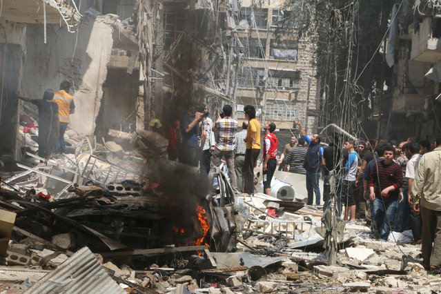 People inspect the damage at a site hit by airstrikes, in the rebel-held area of Aleppo's Bustan al-Qasr, Syria April 28, 2016. (Photo by Abdalrhman Ismail/Reuters)