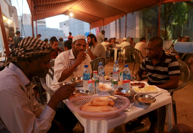 People eat their Iftar (breaking of fast) meal at tables offering free food set up by a charity during the holy fasting month of Ramadan in Benghazi, Libya June 27, 2015. (Photo by Esam Omran Al-Fetori/Reuters)