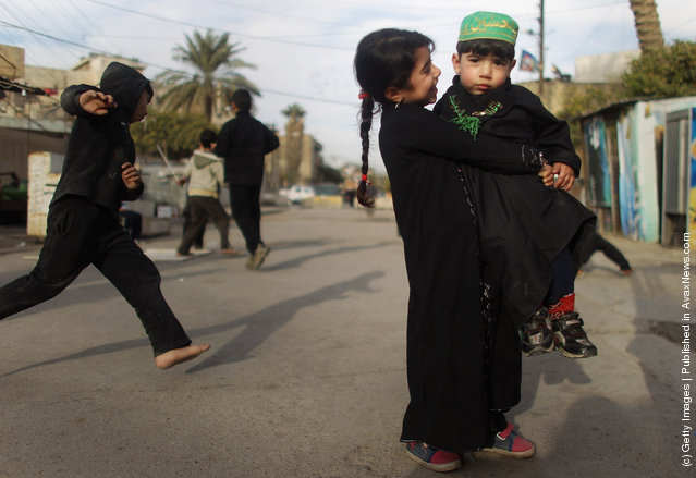 Haneen Muaid holds her brother Aiad Muaid outside Seid Idrees mosque on the day before the festival Ashura