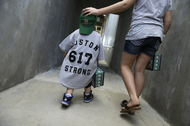 Bryonna Freed walks her little brother,  Boston Sechrist, 2, of Hershey, Pa., off the field before an exhibition baseball game between the Boston Red Sox and the Philadelphia Phillies in Fort Myers, Fla., Saturday, March 15, 2014. (Photo by Gerald Herbert/AP Photo)