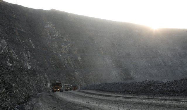 Dump trucks loaded with gold-bearing soil drive at the bottom of the 550-metre-deep Vostochny opencast of the Olimpiada gold operation, owned by Polyus Gold International company, in Krasnoyarsk region, Eastern Siberia, Russia, June 30, 2015. (Photo by Ilya Naymushin/Reuters)