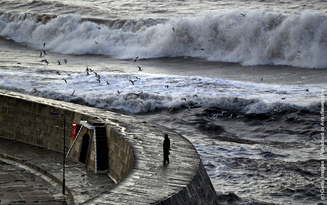 A man walks on the Cobb as storm waves break behind in Lyme Regis, England