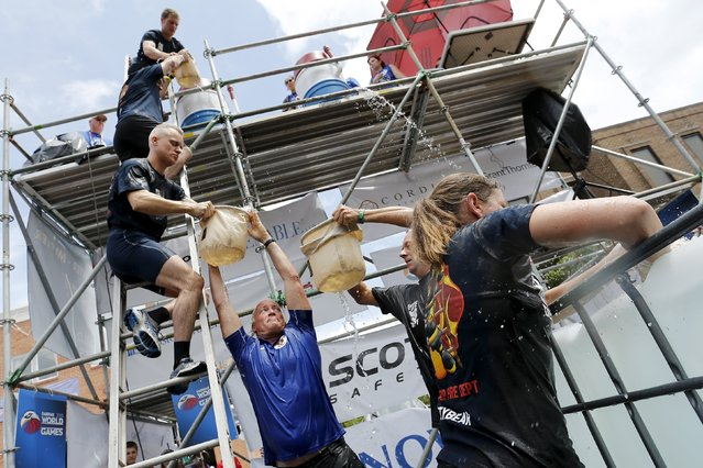 Members of a Belgian team from Antwerp pass 30-pound (13.6 kg) bags of water up the ladder in the bucket brigade competition of the Firefighter Muster event at the World Fire and Police Games in Fairfax, Virginia July 4, 2015. (Photo by Jonathan Ernst/Reuters)