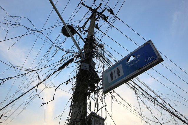 A sign board for a public toilet is seen attached to an electric pole in Guangfuli neighbourhood in Shanghai, China, March 28, 2016. (Photo by Aly Song/Reuters)