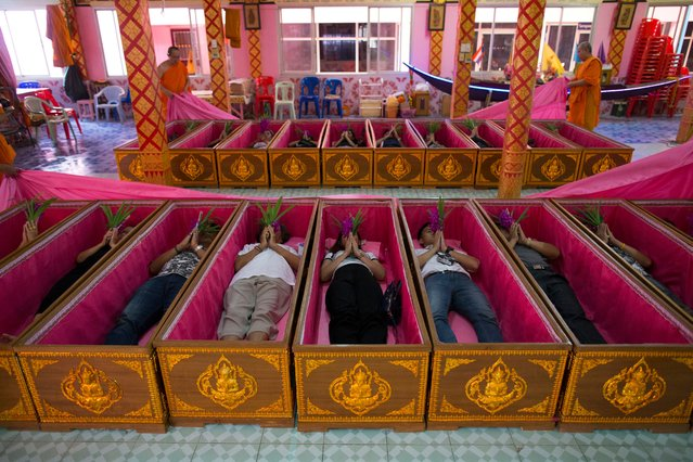 Thai devotees lie inside coffins as Buddhist monks officiate during a coffin ritual at Wat Takien temple in Nonthaburi province, Thailand, 01 April 2017 (issued 02 April 2017). The Buddhist temple offers believers to attend the resurrection ritual by laying down in coffins while monks pass a cloth over them, chant a dirge for the symbolic death and then rise up again believing that they are cleansed of their karma, get rid of bad luck and reborn for a fresh start in life with protection from harm, wealthy, good health and their wishes completely fulfilled. (Photo by Rungroj Yongrit/EPA)