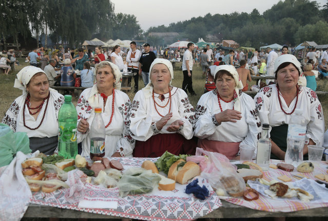 Ukrainians dressed in traditional embroidered clothing, sing folk songs during Midsummer Night pagan celebrations in Kiev, Ukraine late Monday, July 6, 2015. The age-old pagan Slav festival is still celebrated in Ukraine and many people believe that jumping over the fire cleanses them of evil spirits. (Photo by Efrem Lukatsky/AP Photo)