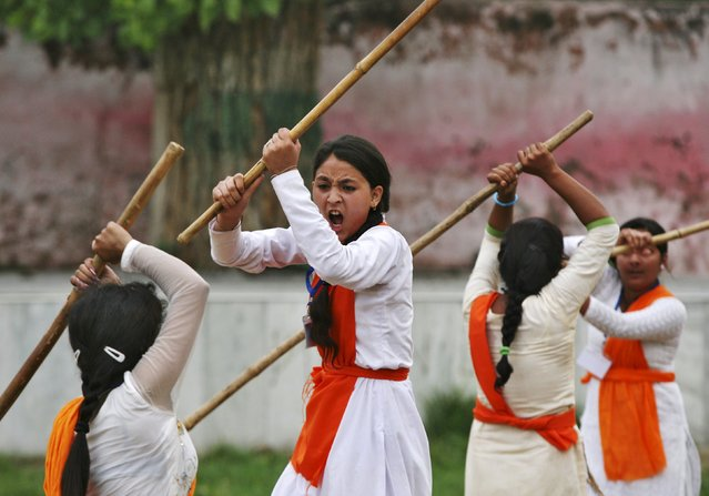 School girls wield bamboo sticks during an event held to demonstrate self-defence skills as part of a camp organized by the Vishwa Hindu Parishad (VHP), a Hindu group, in Jammu July 7, 2015. (Photo by Mukesh Gupta/Reuters)