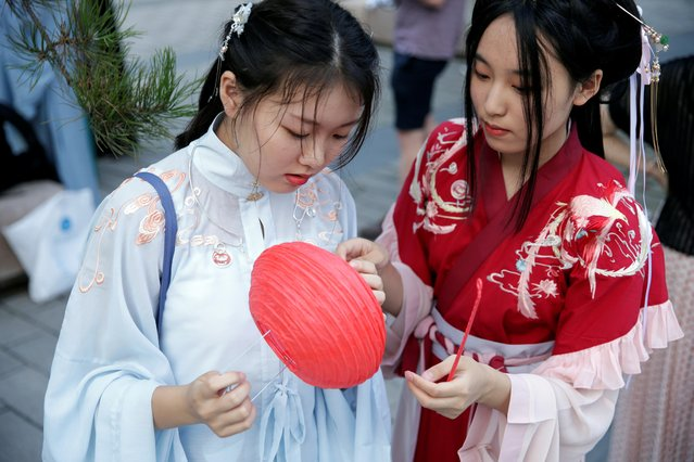 "Girls dressed in ""Hanfu"", or Han clothing, prepare for an event to mark the traditional Qixi festival, the Chinese equivalent of Valentine's Day, at a park in Beijing, China, August 7, 2019. Chinese for ""Han clothing"", ""Hanfu"" is based on the idea of donning costumes worn in bygone eras by China's dominant Han ethnicity. Some of the most popular styles are from the Ming, Song and Tang dynasties. Hanfu enthusiasts doubled to two million in 2018 from a year earlier, according to a survey by Hanfu Zixun, a popular community account on the Wechat social media platform. (Photo by Jason Lee/Reuters)"