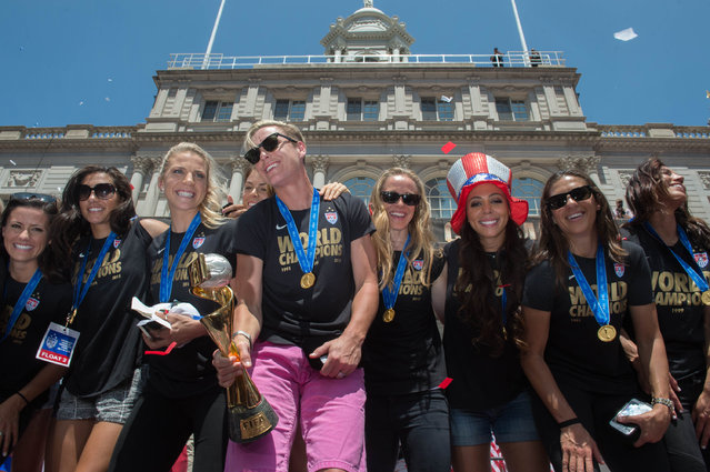 Flanked by her teammates, Abby Wambach holds their trophy at New York's City Hall as the U.S. Women's World Cup soccer champions celebrate following a ticker tape parade up Broadway's Canyon of Heroes, Friday July 10, 2015. (Photo by Bryan R. Smith/AP Photo)