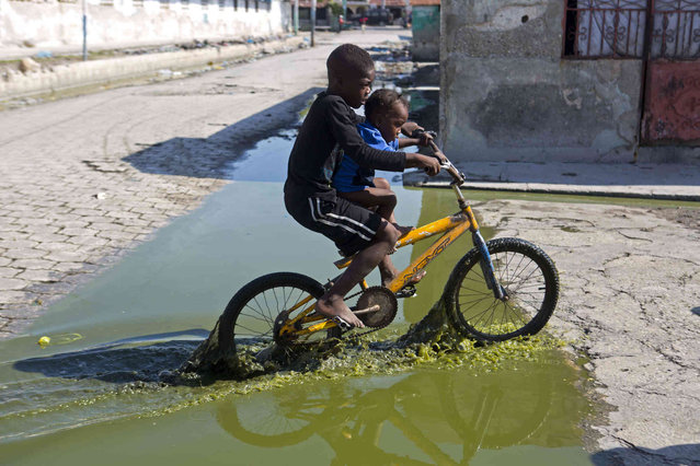 A youth and his little brother navigate across sewage water as they take a bike ride through the Cite Soleil area of Port-au-Prince, Haiti, Sunday, March 17, 2019. (Photo by Dieu Nalio Chery/AP Photo)