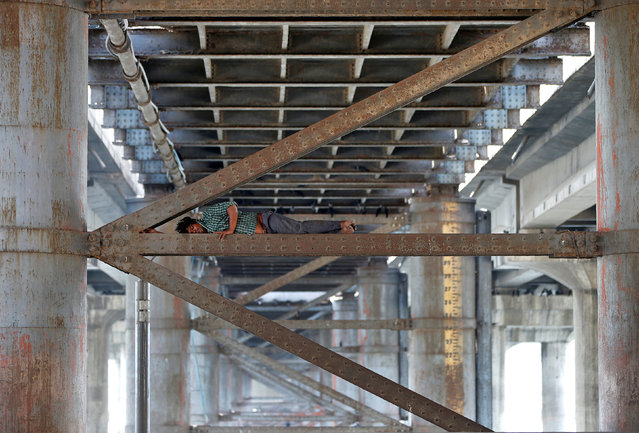 A man rests on a girder between the two pillars of a bridge on the Sabarmati river during a hot summer day in Ahmedabad, April 17, 2017. (Photo by Amit Dave/Reuters)