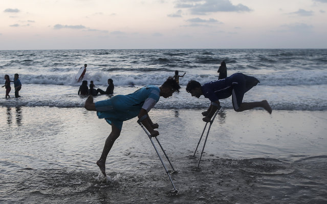 Palestinian amputees Mohammed Eliwa, 17, and Ahmed al-Khoudari (R), 20, who lost their legs during clashes on the border with Israel, play on the beach in Gaza City on August 20, 2019. (Photo by Mahmud Hams/AFP Photo)