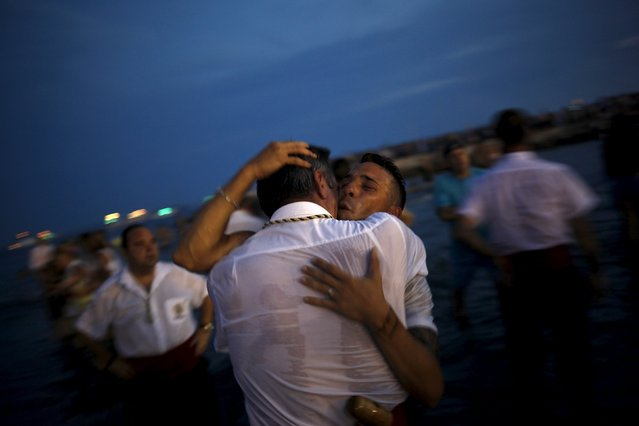 Men in traditional costumes embrace after carrying a statue of the El Carmen Virgin into the sea during a procession in Malaga July 16, 2015. (Photo by Jon Nazca/Reuters)