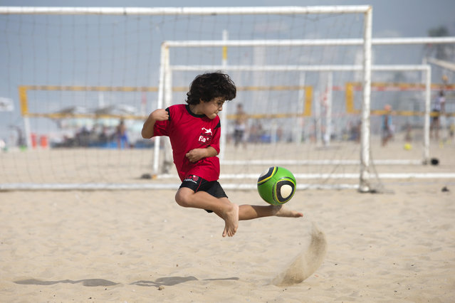 A boy controls the ball as he trains on Ipanema beach in Rio de Janeiro, Brazil, Wednesday, May 7, 2014. The player is a member of the Flamengo club's soccer school which holds their soccer training for young members on the beach. Brazil will host the 2014 World Cup tournament. (Photo by Hassan Ammar/AP Photo)