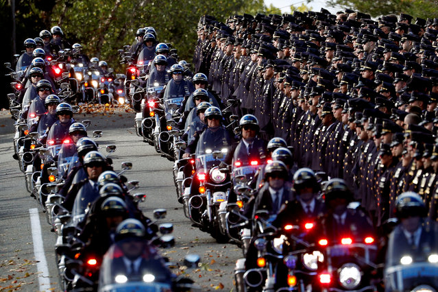 A procession of police motorcycles passes officers lining the street at the funeral service for shot New York City Police Department (NYPD) officer Brian Mulkeen at the Sacred Heart Church in Monroe, New York, U.S., October 4, 2019. (Photo by Mike Segar/Reuters)