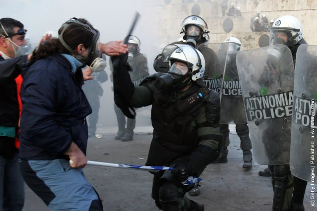 Demonstrators fight with riot police during violent protests on February 12, 2012 in Athens, Greece