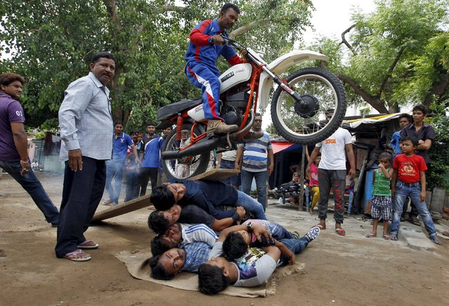 A Hindu devotee performs a stunt with his motorcycle during a rehearsal for the annual Rath Yatra, or chariot procession, in Ahmedabad, India, July 12, 2015. Hindu devotees perform various stunts as part of the annual Rath Yatra celebrations which commemorates a journey by Hindu god Jagannath, his brother Balabhadra and sister Subhadra, in specially made chariots. The annual Rath Yatra is celebrated on July 18. (Photo by Amit Dave/Reuters)