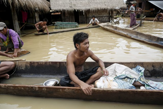 People collect food from local donors at a village in Kawlin township, Sagaing division, Myanmar, July 21, 2015. Heavy rains caused flooding over 20,000 acres of rice field and in about a hundred villages, killing at least eight people, according to local media. (Photo by Soe Zeya Tun/Reuters)