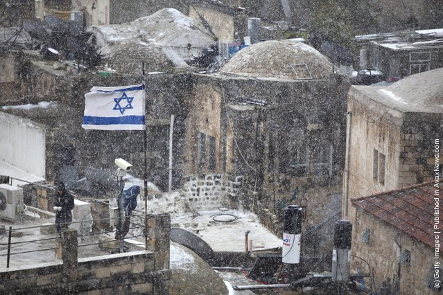 Jewish settlers stand on a rooftop as snow falls on March 2, 2012 in Jerusalem, Israel