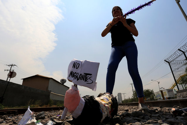 """An activist smiles after hitting a pinata representing U.S. President Donald Trump during a protest to raise awareness of the migrant crossing between Mexico and the U.S., on the outskirts of Monterrey, Mexico May 27, 2017. Pinata sign reads: """"No migrants"""". (Photo by Daniel Becerril/Reuters)"""