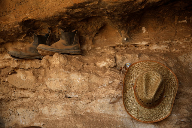 A hat and boots belonging to a volunteer with the Israeli Antique Authority are seen inside the Cave of the Skulls, an excavation site in the Judean Desert near the Dead Sea, Israel June 1, 2016. (Photo by Ronen Zvulun/Reuters)