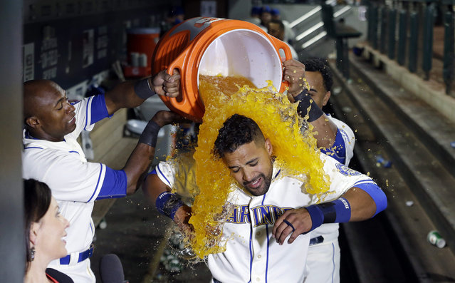 Seattle Mariners' Franklin Gutierrez, center, is doused with a bucket of a sports drink by teammates Austin Jackson, left, and Nelson Cruz after Gutierrez's home run that beat the Toronto Blue Jays in the 10th inning of a baseball game Sunday, July 26, 2015, in Seattle. The Mariners won 6-5. (Photo by Elaine Thompson/AP Photo)