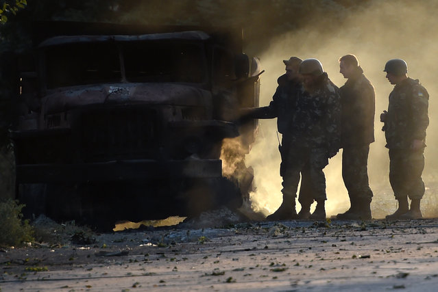 Ukrainian army soldiers check a burnt army truck on September 7, 2014 after an overnight bombing attack, at an Ukrainian army checkpoint in the outskirts of the key southeastern port city of Mariupol. Gunfire and heavy shelling rocked a key frontline city in eastern Ukraine overnight, raising fears on September 7 that a tenuous truce between government and rebel forces had already collapsed. Numerous explosions rattled the night sky and thick smoke was visible on the horizon of Mariupol, a strategic government-held port city on the Azov Sea in the southeast of the country. (Photo by Philippe Desmazes/AFP Photo)