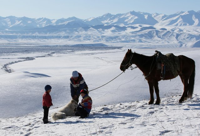 Local residents gather on a slope with a backdrop of the Tien Shan mountains during a traditional hunting contest outside the village of Kaynar in Almaty region, Kazakhstan on December 8, 2019. (Photo by Pavel Mikheyev/Reuters)