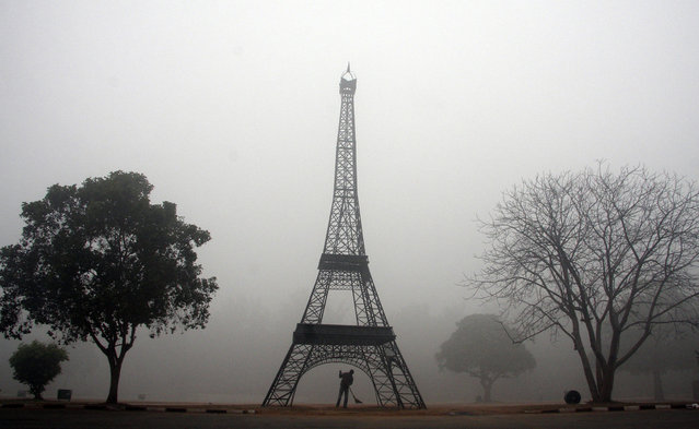 India: A sweeper cleans the side of a road near a replica of the Eiffel Tower amid heavy fog in the early morning in the northern Indian city of Chandigarh January 18, 2010. (Photo by Ajay Verma/Reuters)