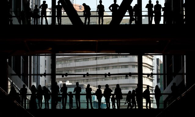 Spectators are silhoutted as they watch the Islamic Fashion Festival during 2014 Malaysia International Fashion Week in Kuala Lumpur on June 20, 2014. (Photo by Manan Vatsyayana/AFP Photo)