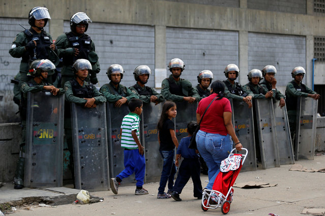 A woman and children walk past Venezuelan national guard officers as locals gather outside a supermarket to try to buy food in Caracas, Venezuela, June 11, 2016. (Photo by Ivan Alvarado/Reuters)
