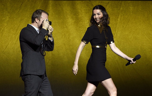 """Rian Johnson, left, director of the upcoming film """"Knives Out"""", takes a picture of cast member Ana de Armas as they are introduced onstage during the Lionsgate presentation at CinemaCon 2019, the official convention of the National Association of Theatre Owners (NATO) at Caesars Palace, Thursday, April 4, 2019, in Las Vegas. (Photo by Chris Pizzello/Invision/AP Photo)"""